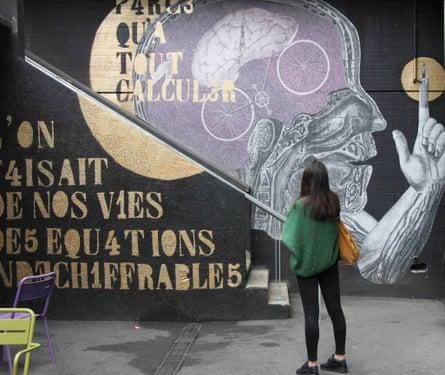 A woman stands in front of street art at Art 42, Batignolles, Paris.