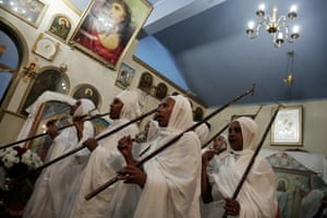 Women of Ethiopian origin sing hymns as they attend the Resurrection Mass, at the Ethiopian Coptic church