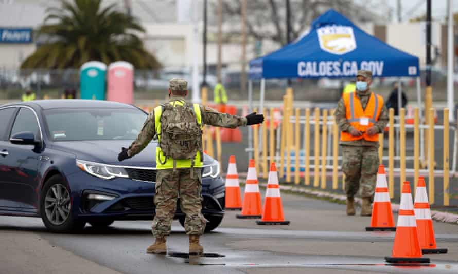 Members of the national guard direct traffic to a drive-through station at the Oakland Coliseum.
