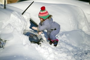 Tess Jorgensson, 3, helps her father dig out their car in Alexandria