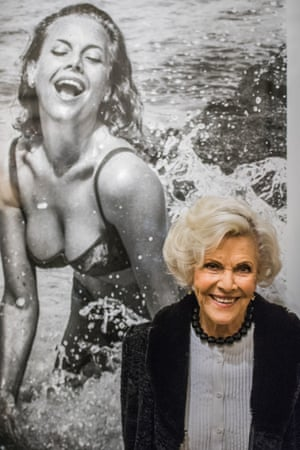 Honor Blackman in front of a photo of her as Pussy Galore by Terry O'Neill