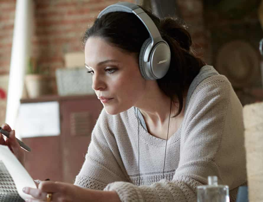 A woman works from home while wearing Bose QC35 wireless headphones
