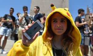 A gamer dressed up like a Pokemon shows her mobile phone.