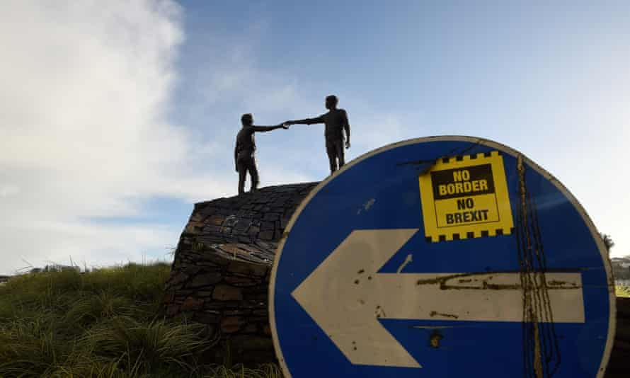 A ' No Border, No Brexit' sticker is seen on a road sign in front of the Peace statue entitled 'Hands Across the Divide' in Londonderry