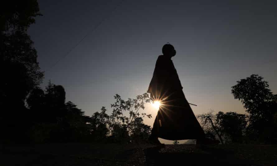 A Buddhist monk walks near the temple of Tsuglagkhang, popularly known as the Dalai Lama temple, at sunset in McLeod Ganj, Dharamsala