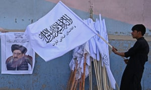 A vendor in Kabul holds a Taliban flag next to a poster of Taliban leader Mullah Abdul Ghani Baradar