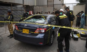 Police examine the car used by alleged gunmen in an attack on the Pakistan stock exchange in Karachi.