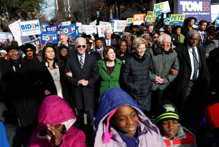 Democratic presidential candidates walk arm-in-arm with local African American leaders during the Martin Luther King Jr Day parade in Columbia, South Carolina, on 20 January.
