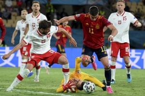 Poland's Bartosz Bereszynski (left), keeper Wojciech Szczesny and Spain's Ferran Torres challenge for the ball.
