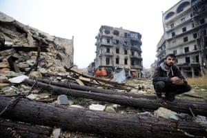 A man sits amid debris near the Umayyad mosque