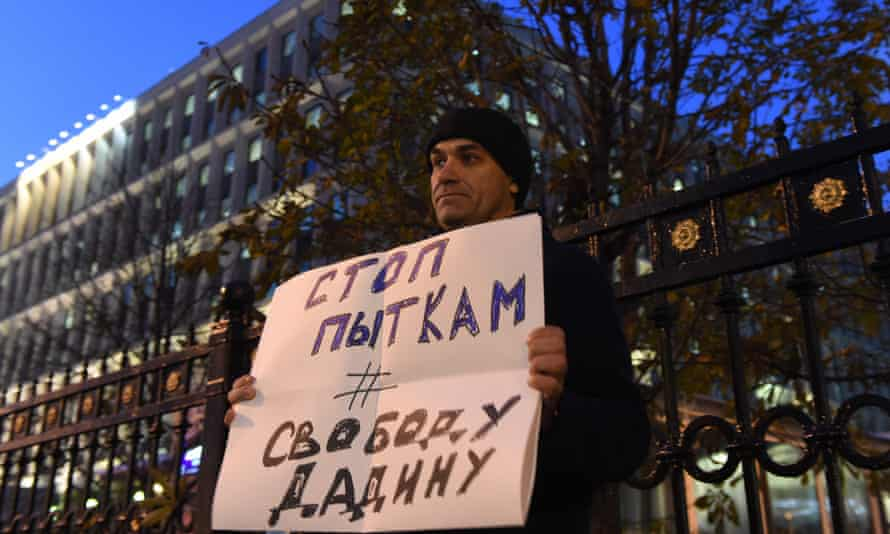 A man holds a placard reading 'Stop torture, freedom for Dadin' as he pickets outside Russia's Federal Penitentiary Service in Moscow.