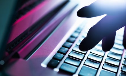 Close up of silhouetted male hand typing on laptop keyboard