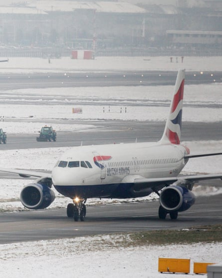A team of snow ploughs are escorted between terminals as a British Airways plane taxis to Terminal 5 of Heathrow Airport in West London
