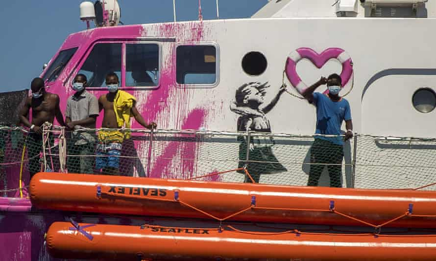 A boy waves from the deck of the Louise Michel rescue vessel, a French patrol boat manned by activists and funded by Banksy.