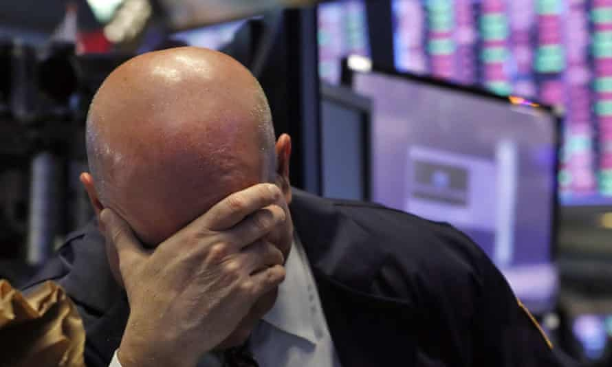 A trader has his head in his hand on the floor of the New York stock exchange