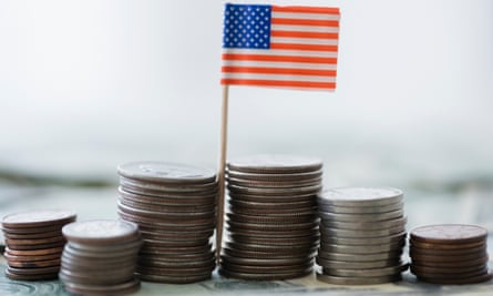 The US flag sits by piles of US coins
