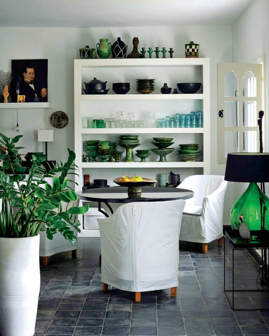 Glassware, ceramics and plants provide green accents in the sitting area by the kitchen