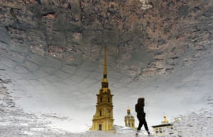 The silhouette of a woman is reflected in a puddle as she crosses a square in front of the Peter and Paul Cathedral in St Petersburg.