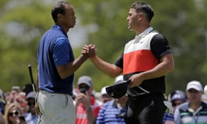 Brooks Koepka, reigning US PGA champion, shakes Tiger Woods's hand after their first round together.