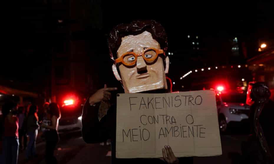 An activist wears a mask depicting Brazil's environment minister, Ricardo Salles