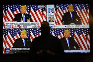 A live broadcast of President Donald Trump speaking from the White House is shown on screens at an election-night party, Tuesday, Nov. 3, 2020, in Las Vegas.