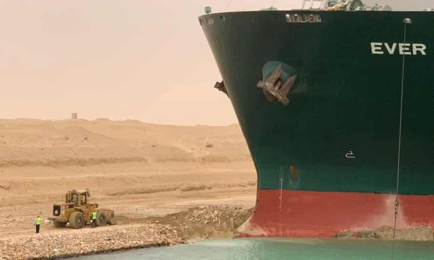 Workers are seen next to a container ship which was hit by strong wind and ran aground in Suez canal