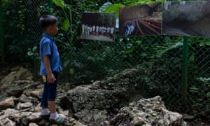 A boy views photos at the entrance of Tham Luang Nang Non Cave