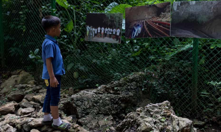 A boy views photos at the entrance of Tham Luang Nang Non Cave