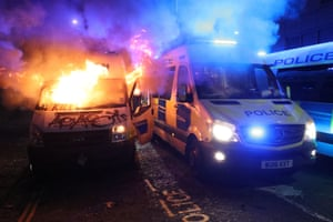 A vandalised police van on fire outside Bridewell police station, as other police vehicles arrive.