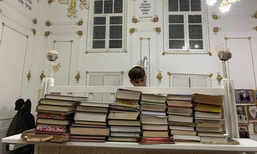 Benyamin Badalov, 15, reads the evening prayer on the first night of Hanukah at the main synagogue in Bukhara.