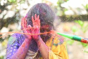 A young girl in Agartala is sprayed with coloured water and powder by her friends