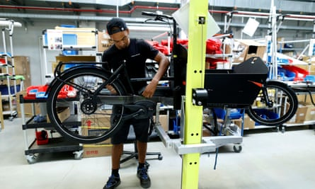 An employee works on an electric cargo bicycle at the production plant of e-bike manufacturer Riese & Mueller in Muehltal, Germany.