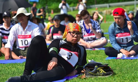 people lie or sit on the grass in a seoul park