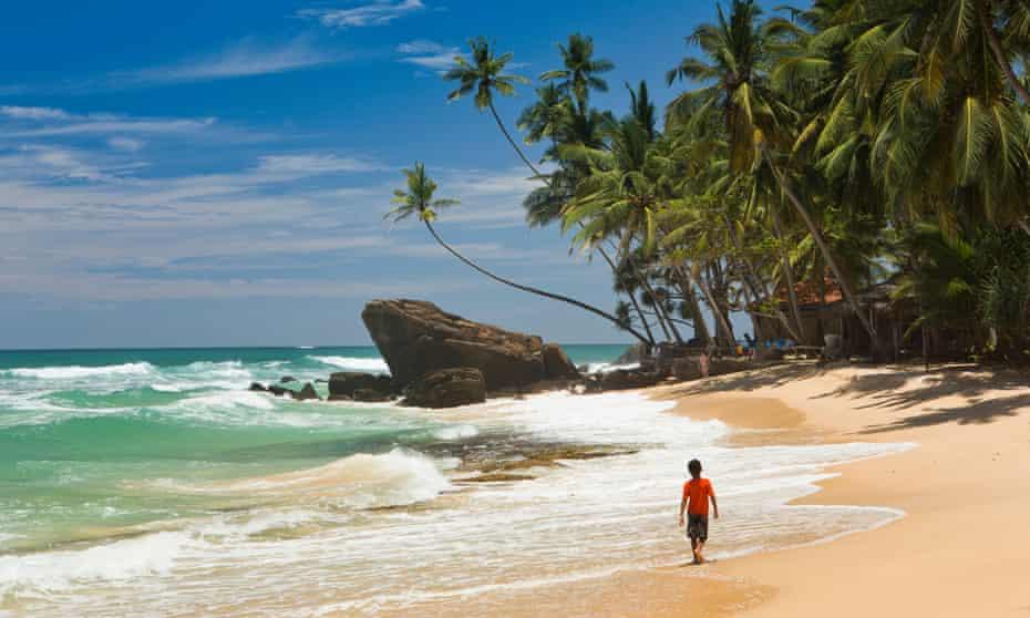 young boy alone walking on tropical Dalawella beach, Galle province, Sri Lanka.