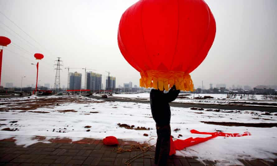 A worker installs lanterns for the official unveiling of a new highway in Luoyang, Henan province.