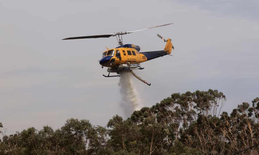 Helicopter water bombing bushfire