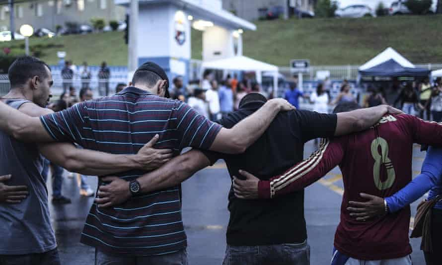 A group of policemen and their relatives pray outside military police headquarters in Vitoria on Wednesday following the funeral of policeman Mario Marcelo Albuquerque, who was killed in the line of duty.