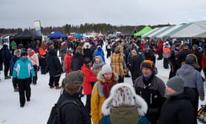 Locals and international visitors gather at stalls selling local crafts, coffee and reindeer meat stew at the race in Inari.