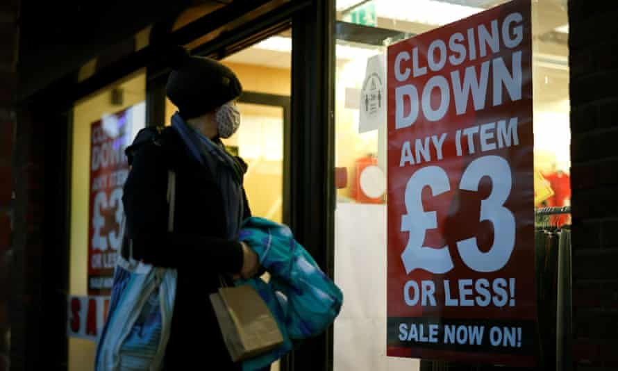 """A shopper wearing a face covering looks in the window of a shop advertising a """"Closing Down"""" sale sign in Walthamstow, north east London."""