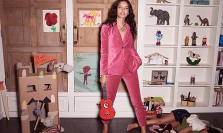 A model in a pink suit in a child's bedroom with a child lying on the floor