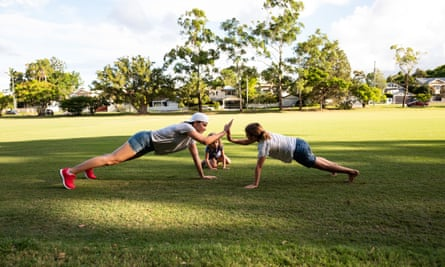 Mother and two daughters exercising in a park together