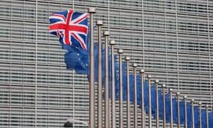 A union jack flag flutters next to EU flags