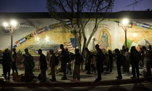 Homeless people wait in line for a meal served by a community organization outside Our Lady Queen of Angels Catholic church in Los Angeles.