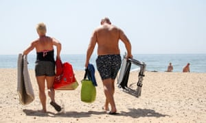 A couple make their way across the sand with their belongings as people enjoy the sunshine and hot weather on Bournemouth beach, Dorset