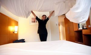 A chambermaid prepares the bed in a guest room.