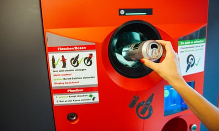 A woman deposits a can into a machine
