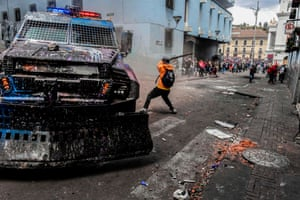 A demonstrator lashes out during clashes with riot police in Quito, as thousands march against Ecuadorean president Lenin Moreno's decision to slash fuel subsidies.