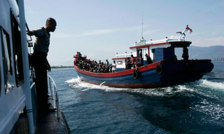 Police guard a wooden boat carrying Rohingya migrants from Burma in April 2013. The migrants, who were heading for Australia, were found stranded on Aceh island.