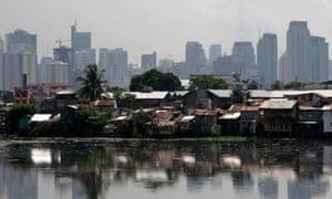 a slum in front of highrises in Manila