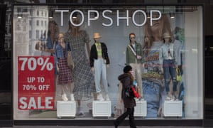 A woman wearing a face mask walks past a closed Topshop store on 21 March 2020 in London.